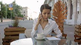 Retrato de sentarse joven de la mujer de negocios relajado en el café de consumición del café al aire libre y de llamar su teléfo almacen de video