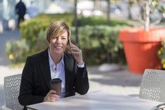Retrato de sentarse de la mujer de negocios relajado en el café al aire libre fotografía de archivo