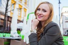 Retrato de sentarse lindo joven de la mujer elegante al aire libre en un café i Foto de archivo libre de regalías