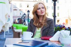Retrato de sentarse lindo joven de la mujer elegante al aire libre en un café i Fotos de archivo