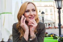 Retrato de sentarse lindo joven de la mujer elegante al aire libre en un café i Fotos de archivo libres de regalías