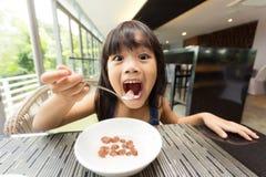 Retrato de sentir feliz a una chica joven que desayuna en la tabla Foto de archivo libre de regalías
