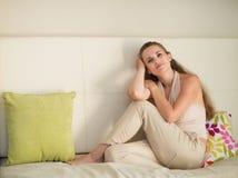 Retrato de soñar a la mujer joven que se sienta en el sofá Foto de archivo