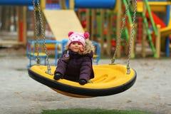 Retrato de sonhar a menina da criança da criança de três anos com cabelo trançado colorido, balanço exterior fotografia de stock
