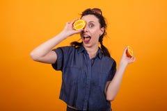 Retrato de sonriente y de recubrimiento joven precioso de su ojo con una naranja fresca y sabrosa en estudio sobre amarillo fotos de archivo