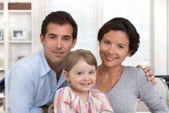Retrato de sorriso da família que senta-se na sala de visitas em casa Imagens de Stock