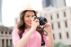 Retrato de sorriso do estilo de vida do verão exterior da jovem mulher bonita que tem o divertimento na cidade em asiático fotos de stock