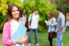 Retrato de sorriso do estudante que guarda um livro Imagens de Stock Royalty Free