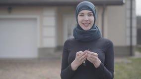 Retrato de sostenerse musulmán joven sonriente independiente de la mujer y de llaves del coche que agitan que llevan el pañuelo t almacen de video