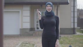 Retrato de sostenerse musulm?n joven sonriente independiente de la mujer y de llaves del coche que agitan que llevan el pa?uelo t metrajes