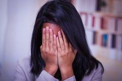 Retrato de sostenerse que se sienta del adolescente deprimido principal en las manos, mujer joven triste subrayada que tiene prob Fotos de archivo libres de regalías
