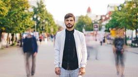 Retrato de time lapse del hombre joven serio que mira la cámara que se coloca en el centro de la calle peatonal ocupada en verano metrajes