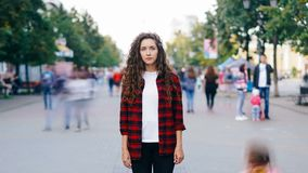 Retrato de time lapse del inconformista serio de la muchacha todavía que se coloca en la calle céntrica, mirando la cámara cuando almacen de metraje de vídeo