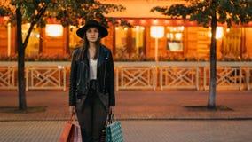 Retrato de time lapse de la mujer hermosa del comprador femenino cansado que se coloca con las bolsas de papel en la calle y que  metrajes