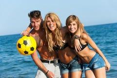 Retrato de três amigos consideráveis na praia. Imagens de Stock