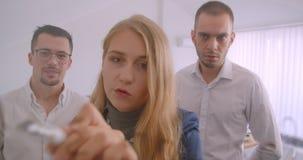 Retrato de três collleagues que trabalham junto no escritório dentro Mulher de negócios bem sucedida que conceitua ideias sobre video estoque