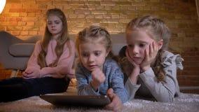 Retrato de três meninas caucasianos pequenas que encontram-se no assoalho e que olham na tabuleta seriamente na atmosfera de casa filme