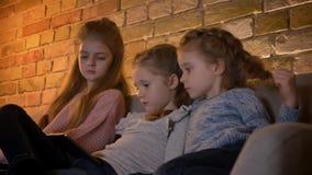 Retrato de três meninas consideravelmente caucasianos que sentam-se no sofá e que olham na tabuleta atentamente na atmosfera de c vídeos de arquivo