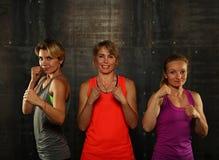 Retrato de três mulheres atléticas novas no gym fotos de stock royalty free