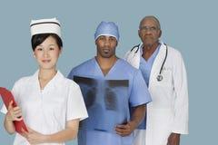Retrato de três multi profissionais médicos étnicos sobre a luz - fundo azul Fotos de Stock Royalty Free