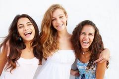 Retrato de tres adolescentes que se inclinan contra la pared imagen de archivo