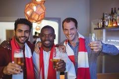Retrato de tres amigos que tuestan los vidrios de cerveza fotos de archivo