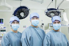 Retrato de tres cirujanos en fila que llevan las máscaras quirúrgicas en la sala de operaciones, mirando la cámara Imagenes de archivo