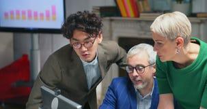 Retrato de tres encargados concentrados que trabajan en nuevo proyecto almacen de metraje de vídeo