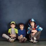 Retrato de tres hermanos en fondo azul Fotos de archivo libres de regalías