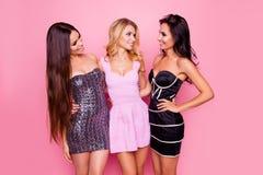 Retrato de tres lindos, muchachas agradables, delgadas, atractivas, en vestidos cortos, mirando el uno al otro, divirtiéndose en  fotos de archivo