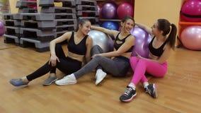 Retrato de tres muchachas atléticas hermosas en el gimnasio almacen de metraje de vídeo