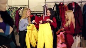 Retrato de tres mujeres jovenes hermosas que hacen compras en una tienda de ropa metrajes