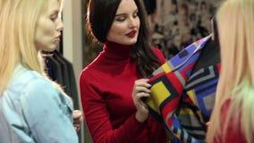 Retrato de tres mujeres jovenes hermosas que hacen compras en una tienda de ropa almacen de metraje de vídeo