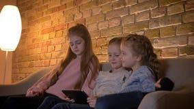Retrato de tres pequeñas muchachas caucásicas que miran en la tableta con atención e interés en atmósfera casera acogedora almacen de metraje de vídeo