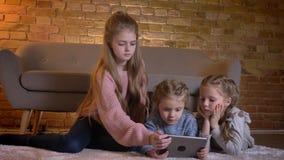 Retrato de tres pequeñas muchachas caucásicas que se sientan en el piso y que miran en la tableta con atención e interés adentro almacen de video