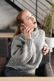 Retrato de um adolescente bonito que relaxa e que usa um telefone celular para ter uma conversação com amigos, sorrindo e imagens de stock