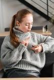 Retrato de um adolescente bonito que relaxa e que usa um telefone celular para ter uma conversação com amigos, sorrindo e foto de stock