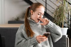 Retrato de um adolescente bonito que relaxa e que usa um telefone celular para ter uma conversação com amigos, sorrindo e fotos de stock