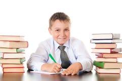Retrato de um adolescente do menino na escola na biblioteca perto da pilha de livros Inventada, veio a inspiração Estudante engra fotografia de stock