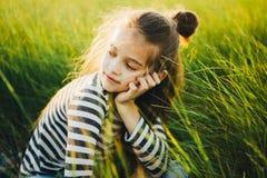 Retrato de um adolescente em um t-shirt listrado entre a grama verde alta imagem de stock royalty free