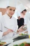 Retrato de um aprendiz de cozimento que prepara o prato Fotografia de Stock