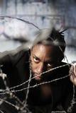 Retrato de um arame farpado da terra arrendada do homem Fotografia de Stock