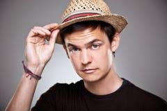Retrato de um assunto normal do menino um chapéu de palha em um fundo cinzento fotos de stock royalty free