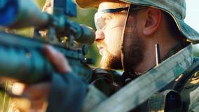 Retrato de um atirador furtivo militar, olhando na vista ótica de um rifle video estoque