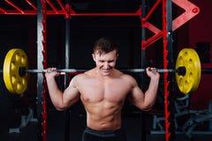 Retrato de um atleta considerável no gym o homem faz o exercício com barbell, posição e squatting seguro grande imagem de stock