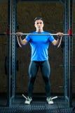 Retrato de um atleta em um t-shirt azul no gym com uma barra r fotografia de stock