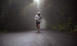 Retrato de um atleta novo que corre na estrada foto de stock