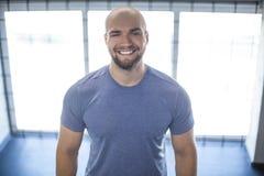 Retrato de um atleta de sorriso novo no gym suportes no fundo de janelas bonitas o exerc?cio era bem sucedido imagens de stock