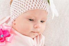 Retrato de um bebê bienal com uma atadura em sua cabeça com uma flor Fotos de Stock