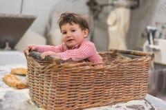 Retrato de um bebê bonito dentro de uma cesta com pão na padaria imagem de stock